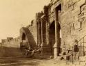 man_in_wagon_at_roman_arch_at_tebessa_algeria._1860-1890